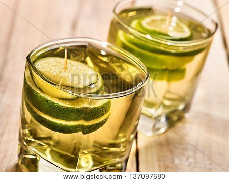 Alcohol drink. On wooden boards are two glasses with alcohol green transparent drink. A drink number sixteen cocktail green tea with lime. Country life. Light background.