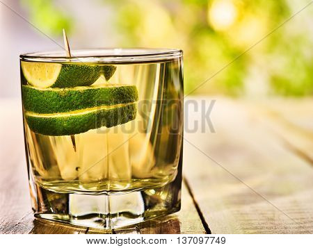 Alcohol drink. On wooden boards is glass with alcohol green transparent drink. A drink number seven cocktail green tea with slice lime. Country life. Light background.