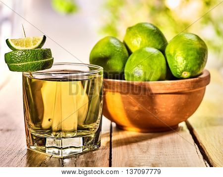 Country drink. On wooden boards is glass with green transparent drink and lime glue bowl. A drink number six . Country life. Light background.