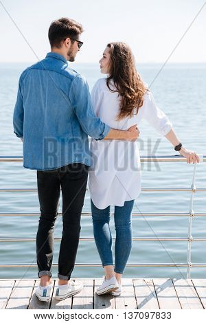 Full length of a young couple standing backwards hugging and looking at each other at the seaside