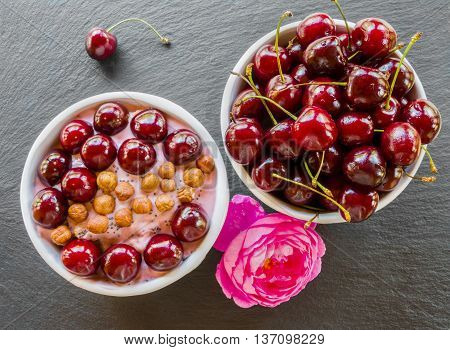 Breakfast bowl with yogurt granola or muesli or oat flakes fresh cherries and nuts. Black stone background pink rose flower. Top view.