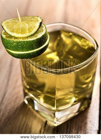 Alcohol drink. On wooden boards is glass with alcohol green transparent drink. A drink number three cocktail green tea with lime. Country life. Light background.