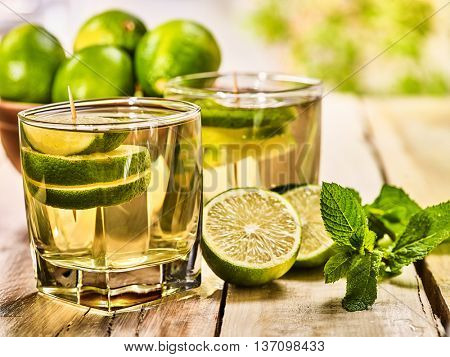 Country drink. On wooden boards are two glasses with green transparent drink and lime glue bowl. A drink number nineteen mojito with mint leaf on sunlight . Country life. Light background.