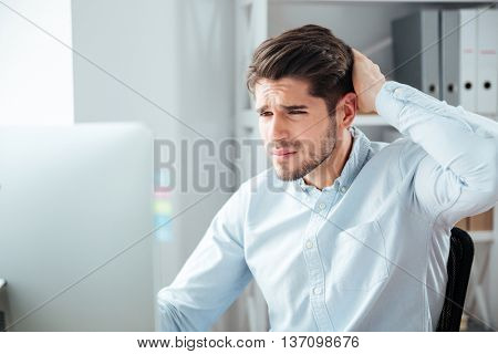Young thoughtful handsome bearded businessman in blue shirt sitting at the table with laptop in office