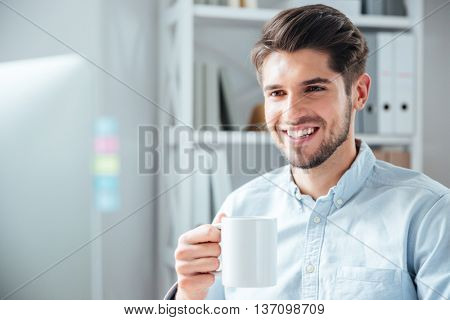 Close-up portrait of a young smiling businessman with cup in office