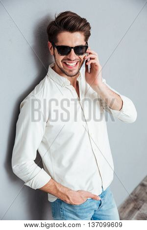 Cheerful attractive young man in white shirt and sunglasses talking on mobile phone over grey background