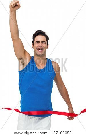 Portrait of cheerful winner athlete crossing finish line with arms raised on white background