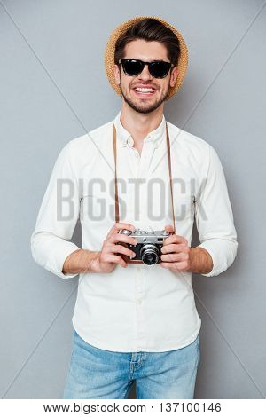 Portrait of cheerful young man in hat and sunglasses holding old camera over grey background