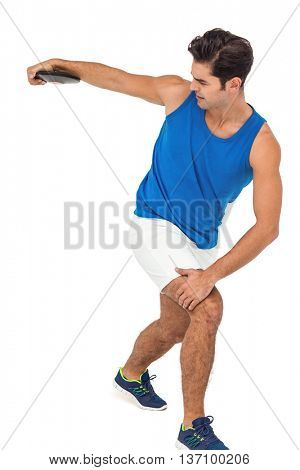 Determined male athlete playing discus throw on white background