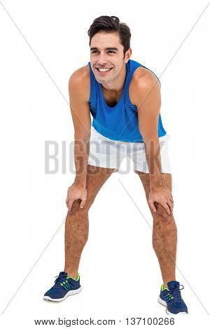 Happy male athlete standing with hand on knee on white background