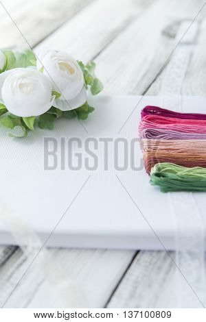 Materials for crosstitching on white wooden background selective focus rustic style