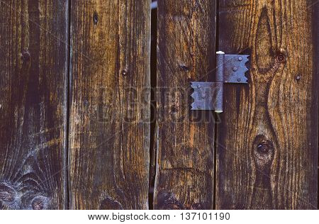 old rusty hinge on wooden door .