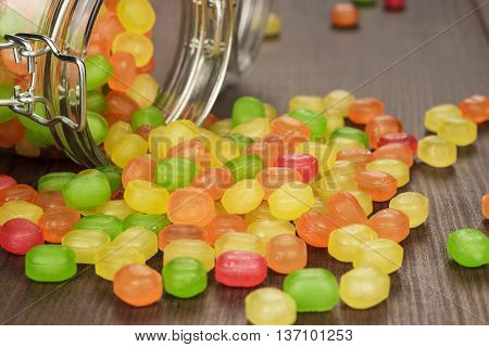toppled over glass jar full of colorful sweets on the wooden table