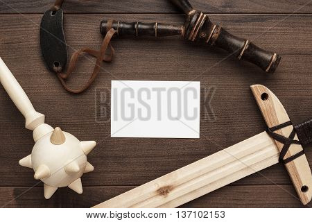 handmade wooden training toy sword, mace and slingshot on the table with copyspace