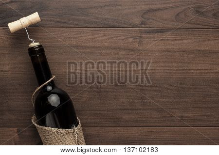 red wine bottle and corkscrew on wooden table background