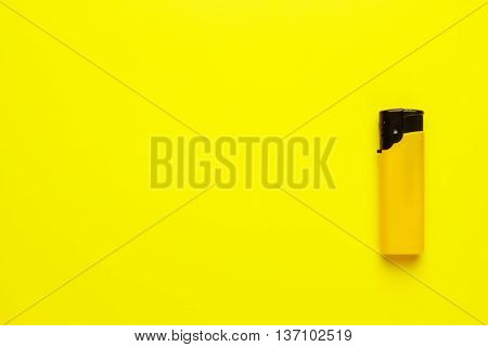 disposable plastic lighter on the yellow background