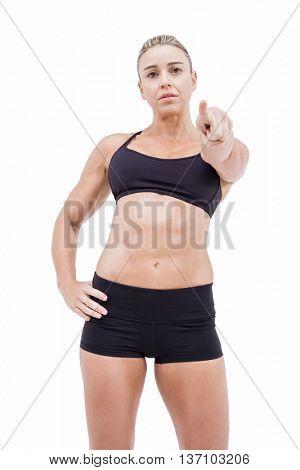 Female athlete pointing the camera on white background