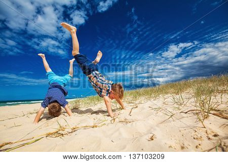 Two young happy boys having fun on tropical beach, doing hand stands
