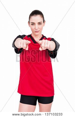 Female athlete posing with elbow pad and pointing the camera on white background