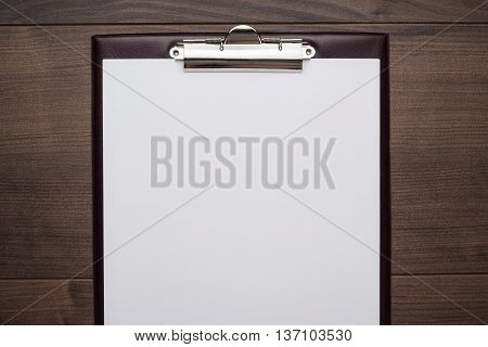 view from above. brown wooden office table with notepad