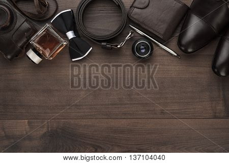 men's accessories in order on the brown wooden table overhead view with copy space