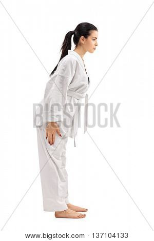 Full length profile shot of a female martial artist bowing isolated on white background