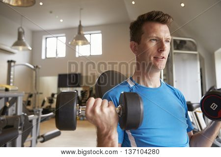 Man practicing bicep curls with dumbbells at a gym, close up