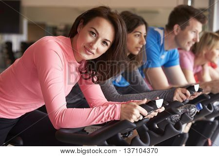 Woman in spinning class at a gym turns and smiles to camera