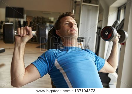 Man works out with dumbbells on a bench at a gym, front view