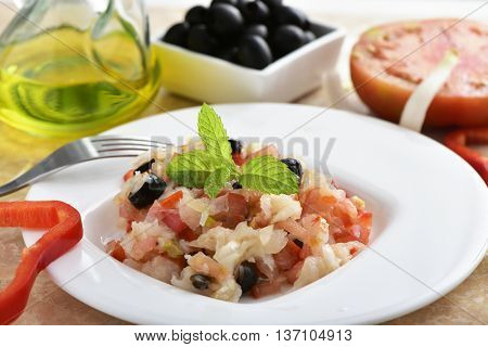 closeup of a dish of esqueixada de bacalla, a cold dish made with codfish, red pepper, tomato, onion and black olives, and dressed with olive oil, typical of Catalonia, Spain, on a table
