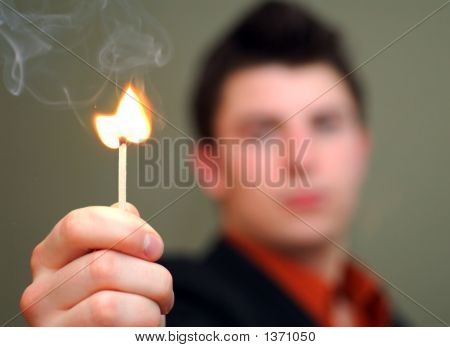 Young Man Holding Flaring Match