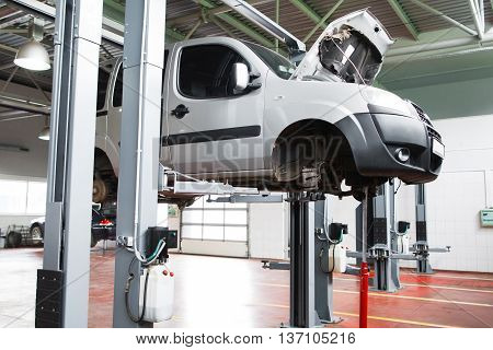 Car undergoing service in garage raised on lift. Front view on gray car without wheels raised on lift in garage with open hood. Auto service industry concept