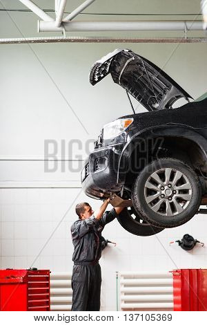Mechanic working under raised car in service station. Mechanic disassemble lifted on hoist car. Young male mechanic repairing SUV car in garage