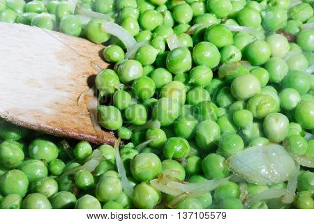 green peas cooked with onions in pan with a wooden spoon