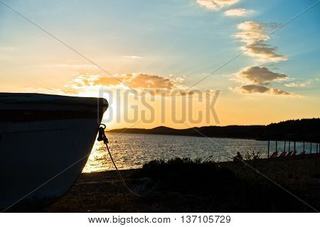 Silhouette of a boat on a beach at sunset in Sithonia, Greece