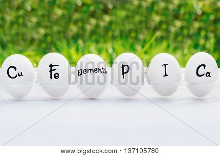 Chicken egg whole in a row with inscription of elements, which eggs include