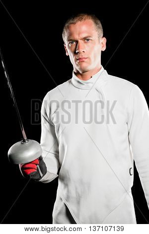 Portrait of swordsman holding fencing sword on black background