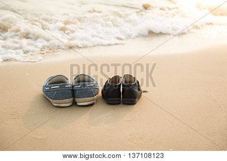 Father's shoes and son's shoes on the beachvintage filter