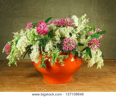 Still life. Meadowsweet alfalfa. Bouquet of meadow flowers in orange pots standing on a wooden table. Rustic style.