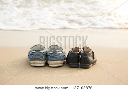 Farther's shoes and son's shoes on the beach vintage filter