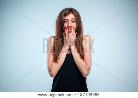 Portrait of young woman with shocked facial expression on gray