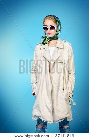 Elegant young woman wearing white coat, sunglasses and headscarf posing at studio. Beauty, fashion.