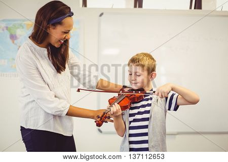 Teacher assisting a schoolboy to play a violin in classroom at school
