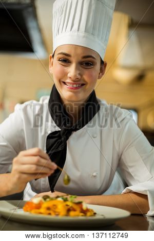 portrait of head chef garnishing pasta dish with olive in commercial kitchen