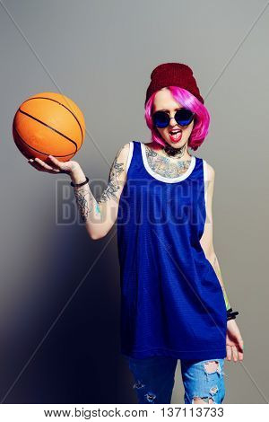 Style of modern youth. Bright girl in sports shirt holding basketball. Tattoo style. Hair coloring.