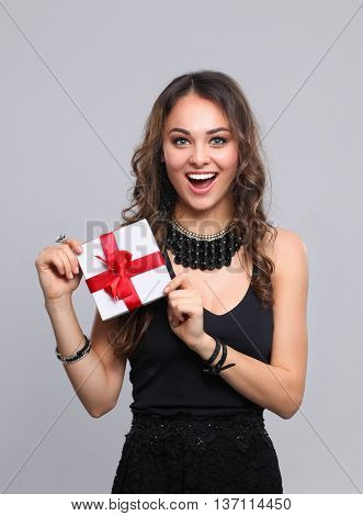 Young woman happy smile hold gift box in hands, isolated over gray background