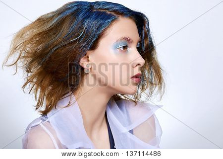 Girl with blue makeup and dyed hair decorated eyebrows strobing face-sculpting pearl earring in a transparent shirt.