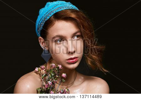 Portrait of the girl with dewy makeup in a blue arabic headband and dried roses