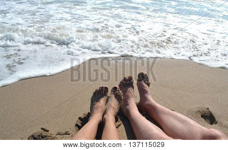 Male and female legs on the beach