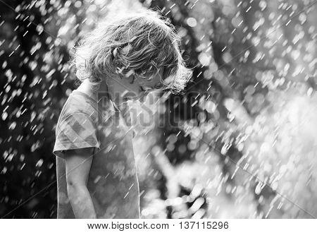 Photo of happy little girl standing under summer rain. Black and white.